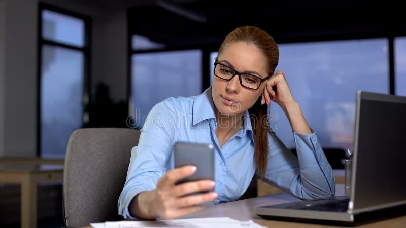 Lat kvinna som använder telefonen, i stället för att göra jobbet på datoren, unproductivitybegrepp arkivbild