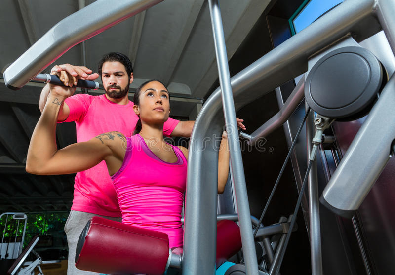 Lat Lateral dorsal pulldown machine upper back. Women with personal trainer man stock photography