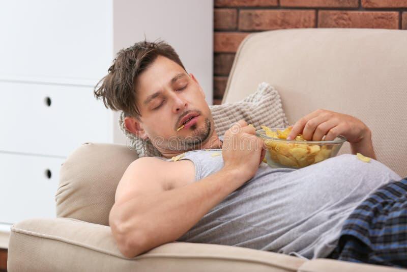 Lat man med bunken av chiper som sover på soffan royaltyfri foto