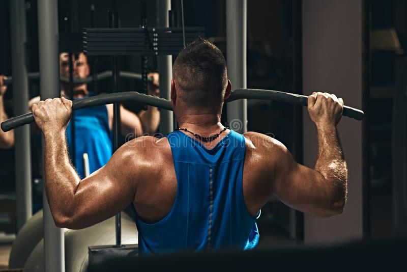 Lat pulldown exercise. Strong male bodybuilder doing exercise for back with lat pulldown machine in gym stock photo