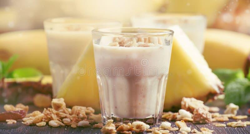 Lat smoothies z bananem, ananasem i granola, ciemny kuchennego stołu tło, selekcyjna ostrość fotografia stock
