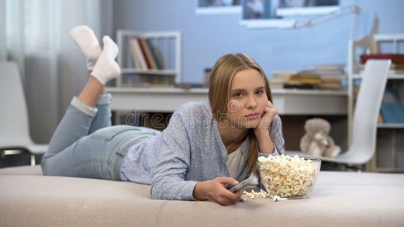 Lat tärande tid för ung kvinna framme av hem- television, ändrande kanaler arkivfoto