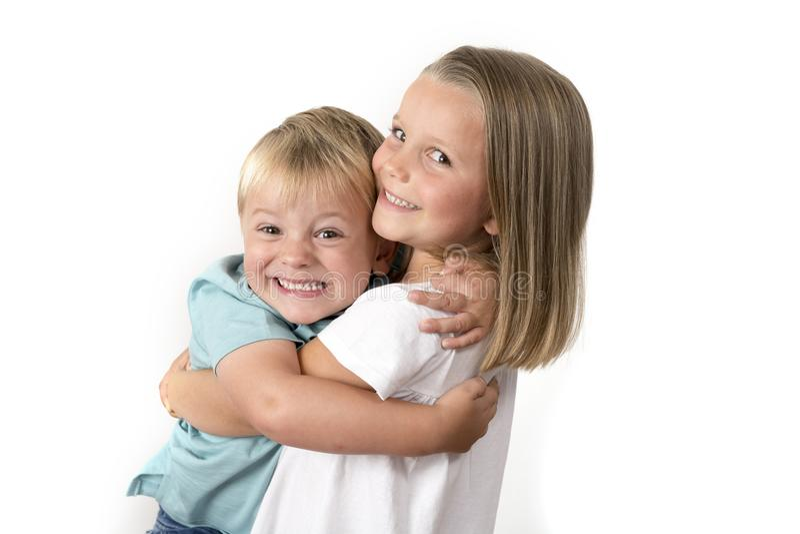 7 lat urocza blond szczęśliwa dziewczyna pozuje z jej małym 3 lat bratem uśmiecha się rozochocony odosobnionego na białym tle zdjęcia royalty free