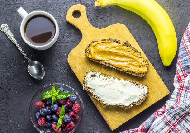 Lata śniadanie: kanapki grzanka z masłem orzechowym lub kremowym serem z malinkami i czarną jagodą, banan obraz stock