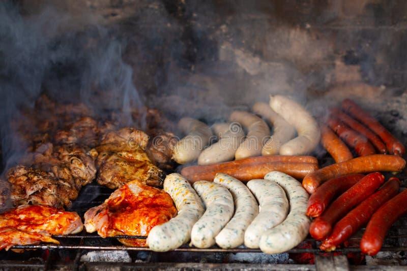 Lata życia stylu pojęcia punktu ostrości asortymentu grilla kiełbasy i mięso piec na grillu w plenerowym ceglanym grillu fotografia stock