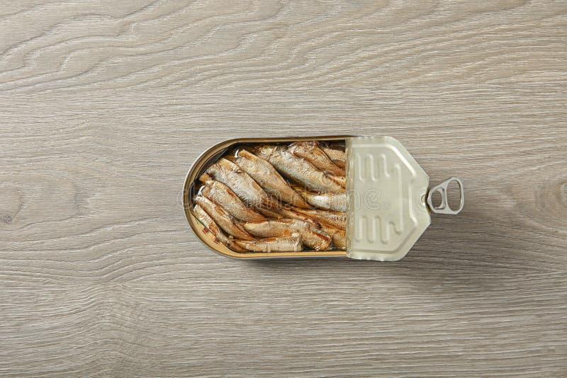 Lata abierta de espadines en fondo de madera foto de archivo