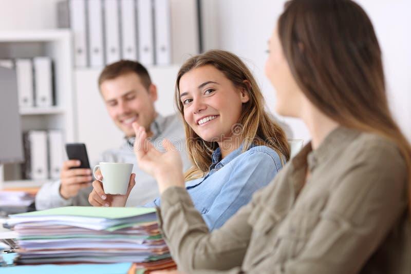 Lata anställda som talar och slöser bort tid på kontoret royaltyfria foton