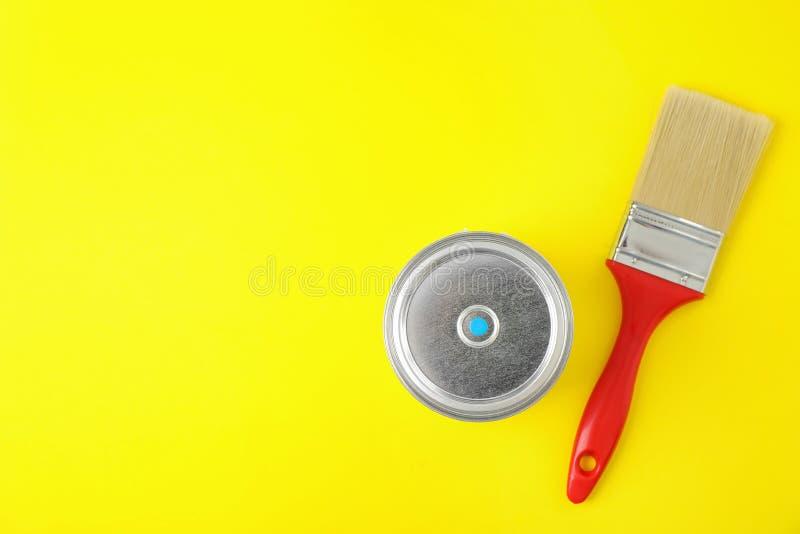 Lata Closed da pintura com a escova no fundo amarelo, vista superior fotografia de stock royalty free