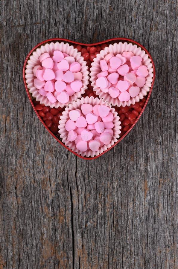 Lata da forma do coração com corações dos doces do rosa do dia de Valentim imagem de stock