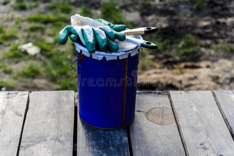 lata da pintura que encontra-se no terraço de uma casa privada com uma escova e as luvas, pronto para ser aberto e pintado reparo imagem de stock royalty free
