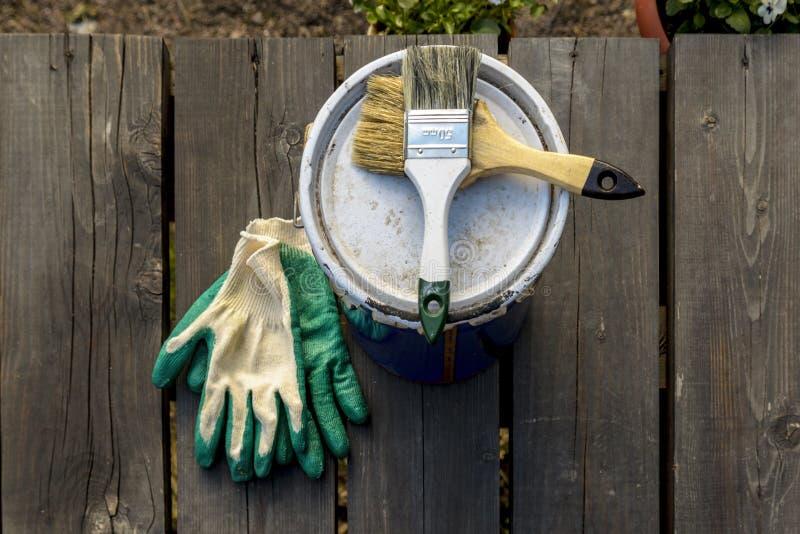 lata da pintura que encontra-se no terra?o de uma casa privada com uma escova e as luvas, pronto para ser aberto e pintado reparo imagem de stock
