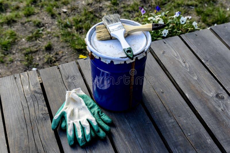 lata da pintura que encontra-se no terra?o de uma casa privada com uma escova e as luvas, pronto para ser aberto e pintado reparo foto de stock royalty free