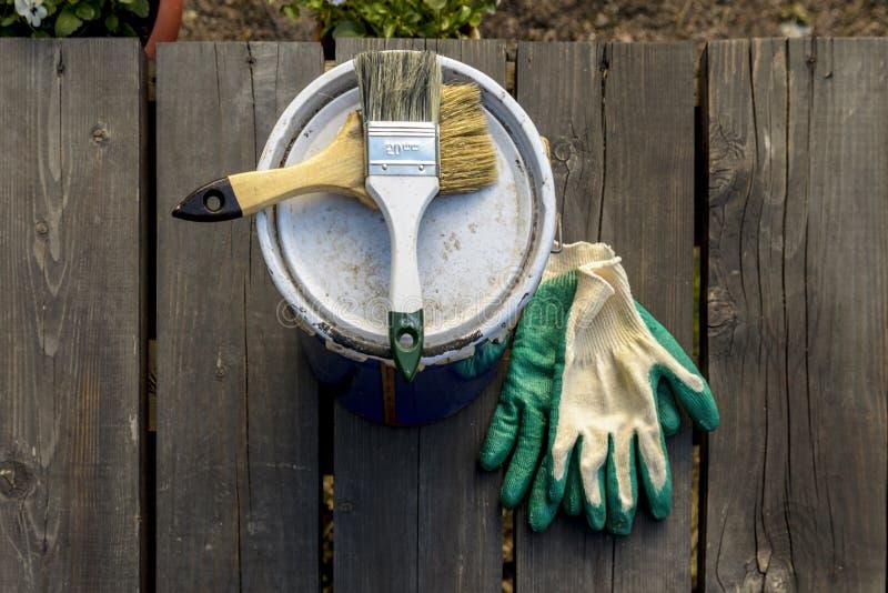 lata da pintura que encontra-se no terra?o de uma casa privada com uma escova e as luvas, pronto para ser aberto e pintado reparo fotos de stock royalty free