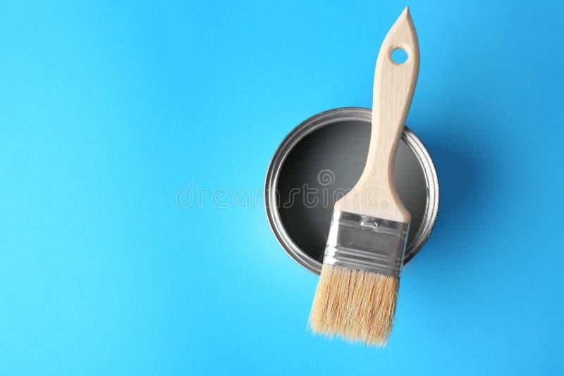 Lata de lata com pintura cinzenta e escova no fundo da cor imagens de stock royalty free
