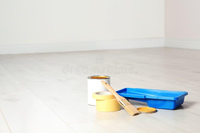 Lata de ferramentas da pintura e do decorador no assoalho de madeira dentro fotos de stock