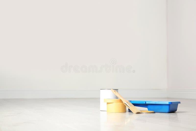 Lata de ferramentas da pintura e do decorador no assoalho de madeira dentro imagem de stock