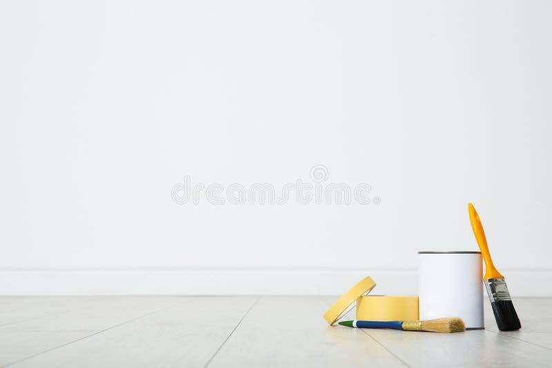 Lata de ferramentas da pintura e do decorador no assoalho de madeira dentro imagens de stock