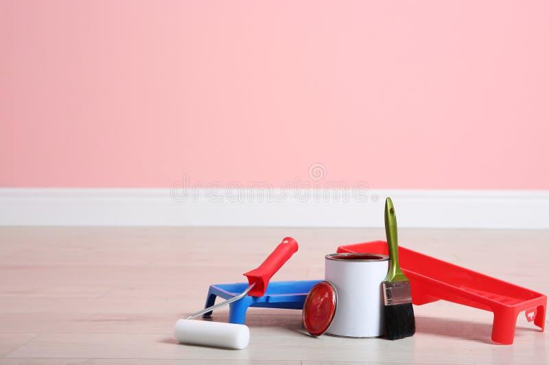 Lata de ferramentas da pintura e do decorador no assoalho de madeira dentro fotos de stock royalty free