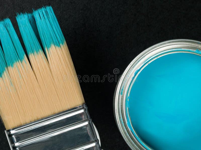Lata de la pintura azul con una brocha fotos de archivo