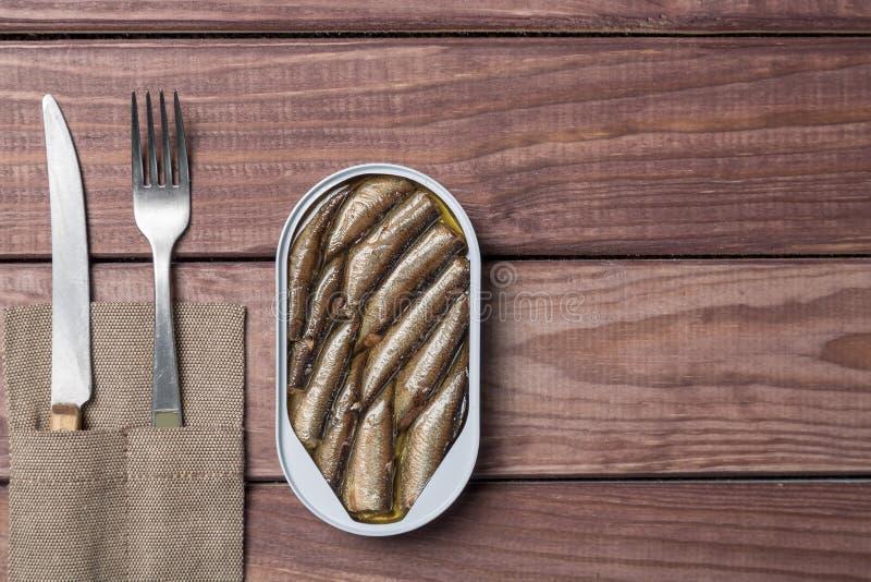 A lata de lata dos arenques pequenos pesca, sardinhas com faca e forquilha na tabela de madeira Vista superior e espaço livre fotografia de stock royalty free