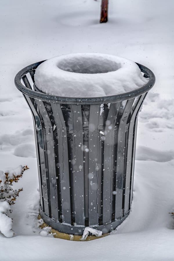 Lata de lixo na terra coberto de neve no inverno imagem de stock