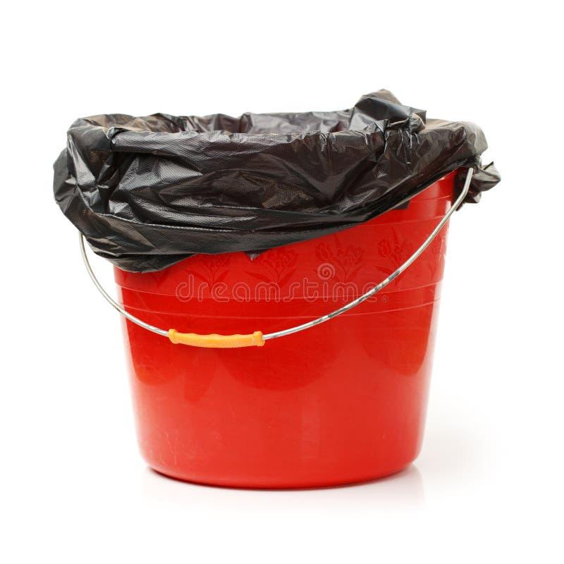 Lata de lixo vermelha e saco de lixo preto foto de stock