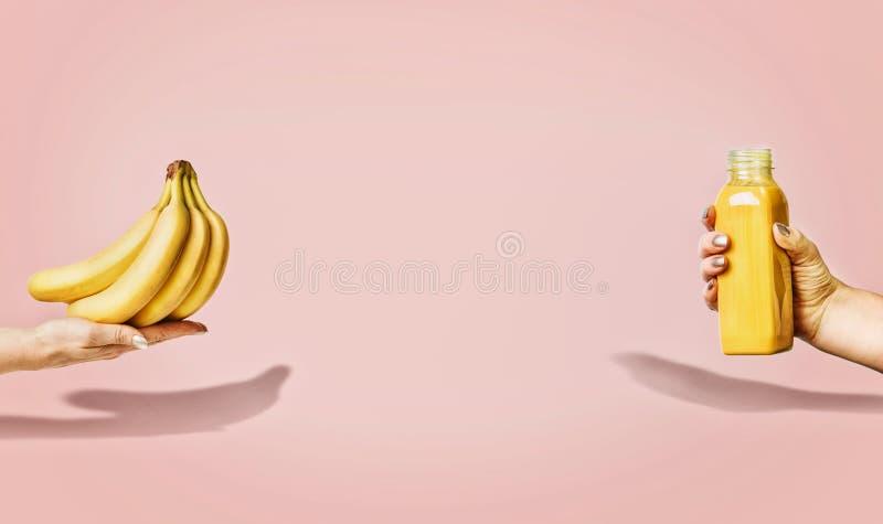 Lata jedzenie i napoju tło z bananami i żółtą napój butelką w żeńskiej ręce przy pastelowymi menchiami obrazy stock