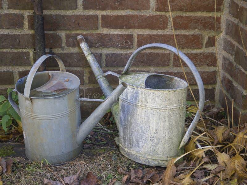 Lata molhando da lata dois oxidada velha na parede do cemitério fotografia de stock royalty free