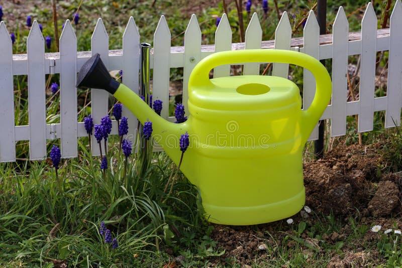 A lata molhando do jardim está na cerca decorativa fotografia de stock