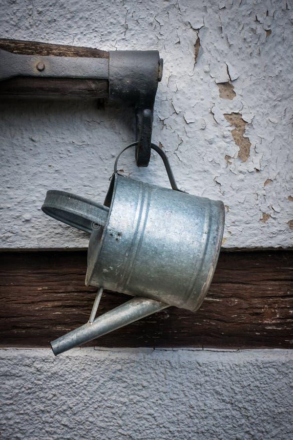 A lata molhando e o balancim velhos na parede da casa da quinta fotografia de stock