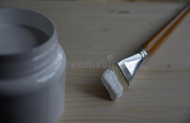 Lata plástica com primeira demão acrílica branca e uma escova de cerda em um painel de madeira Preparando a superfície para tirar fotografia de stock royalty free