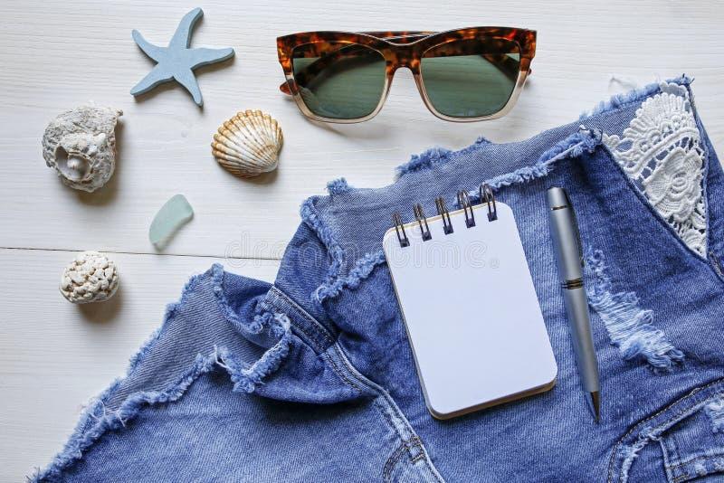 Lata pojęcia planistyczni cajgi zwierają, okulary przeciwsłoneczni, seashells i notatnik, obrazy stock