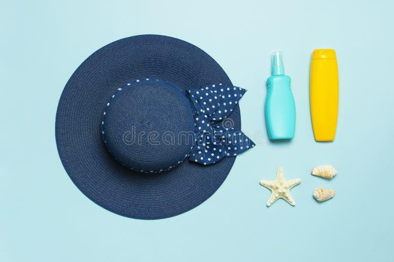 Lata poj?cie, morski t?o Seashells, rozgwiazda, żeński słomiany kapelusz, sunscreen ciała śmietanki kiść na pastelowym błękitnym  obraz stock
