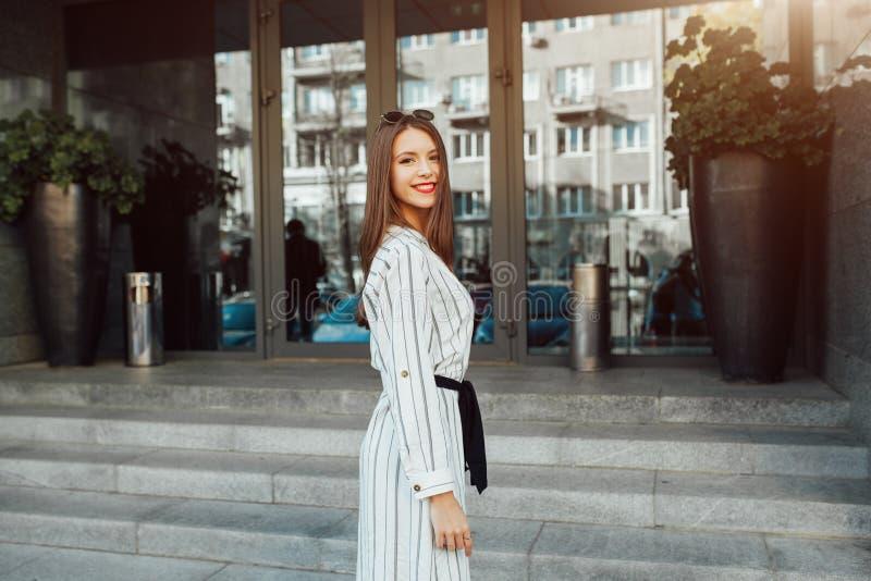 Lata styl życia mody pogodny portret młoda elegancka modniś kobieta chodzi na ulicie z okularami przeciwsłonecznymi, jest ubranym zdjęcia stock