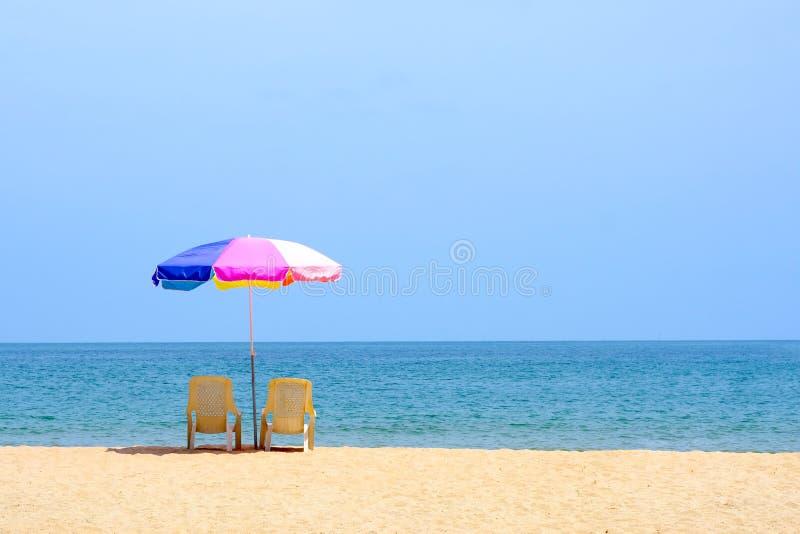 Lata t?o, krzes?o i kolorowy parasol na tle z kopii przestrzeni?, pla?owym i dennym fotografia royalty free
