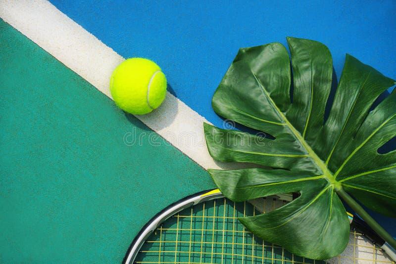 Lata tropikalny tenisowy pojęcie z zielonym monstera liściem i piłką, racquet na ciężkim tenisowym sądzie zdjęcia stock