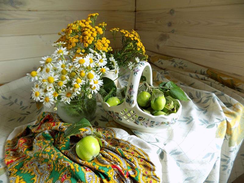 Lata wciąż życie robić łozinowy kosz, dzicy kwiaty i zieleni jabłka, zdjęcie stock