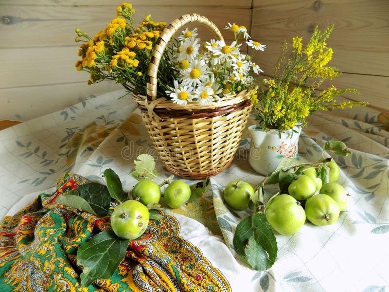 Lata wciąż życie robić łozinowy kosz, dzicy kwiaty i zieleni jabłka, zdjęcia royalty free