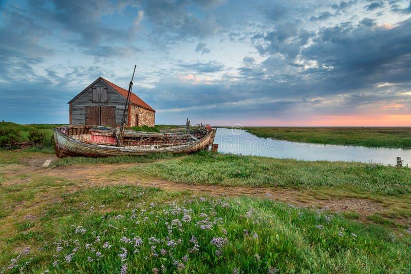 Lata wschód słońca nad starą węglową łodzią rybacką przy Thornham i stajnią obrazy stock