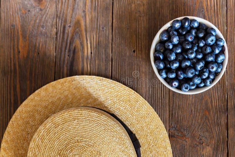 Lata zakończenie czarne jagody i słomiany kapelusz na rocznika drewnianym tle obraz stock