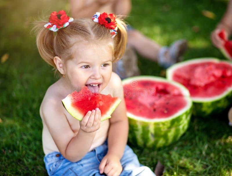 Lata zdrowy jedzenie Lata zdrowy jedzenie dwa dziecka łasowania szczęśliwy uśmiechnięty arbuz w parku Zbliżenie portret śliczne m obrazy stock