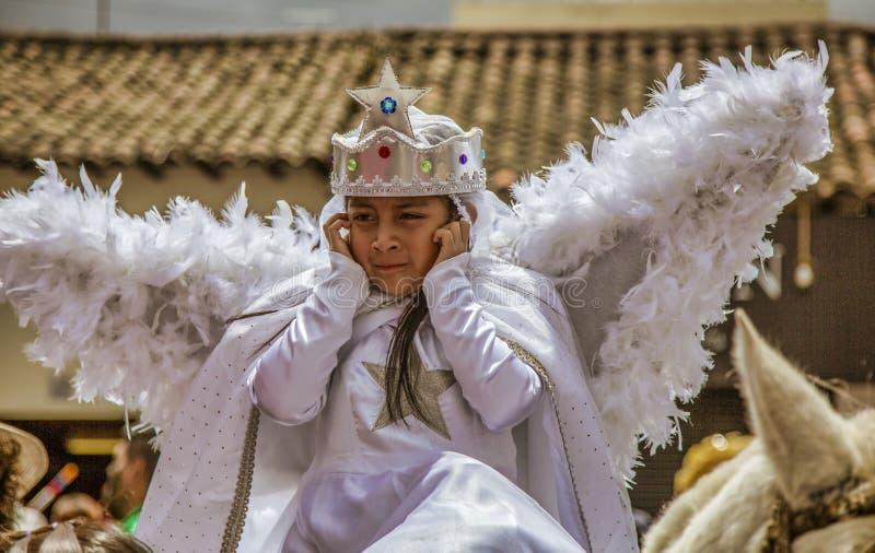 Latacunga Ecuador - September 22, 2018 - flickan i ängeldräkt rymmer hennes öron mot de höga oväsenen av mamman Negra arkivbilder