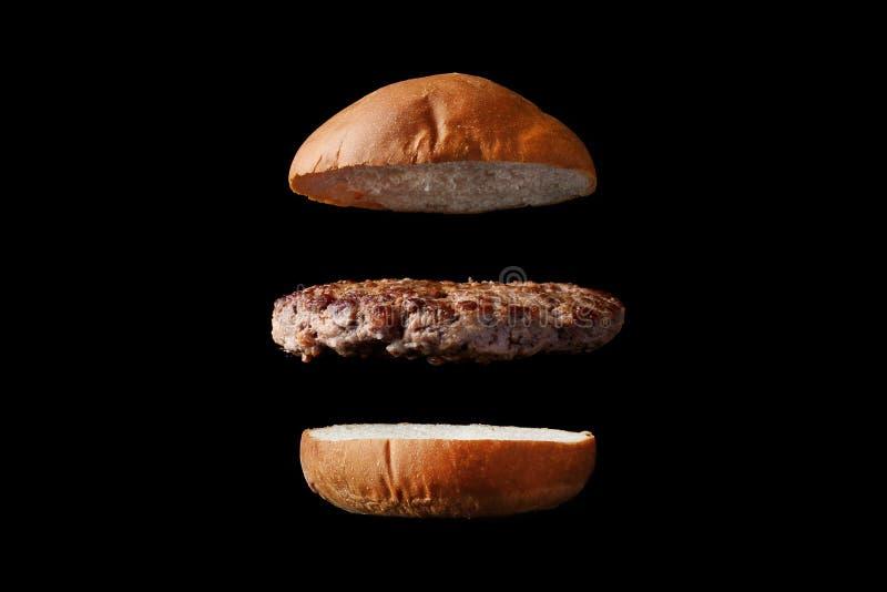 Latający hamburger z babeczką i pasztecikiem odizolowywającymi na czarnym tle obrazy royalty free