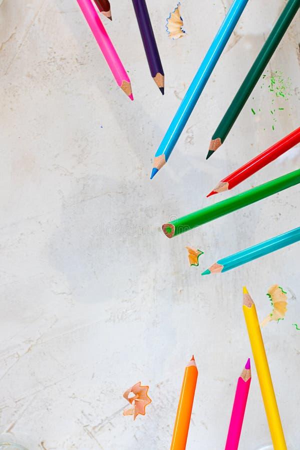 Latający pecils różni kolory i jaskrawe wiórkarki na cemencie siwieją tło, obciosują strzał z kopii przestrzenią dla, teksta i pr zdjęcie royalty free