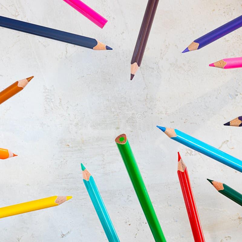 Latający pecils różni kolory na cemencie siwieją tło, obciosują strzał z kopii przestrzenią dla, teksta i projekta, tapeta dla sz obrazy stock