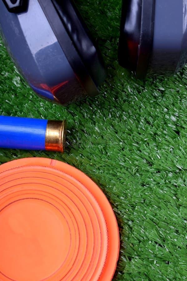 Latający celu talerz, hałasów hełmofonów stłumienie i patron na trawie, zdjęcie royalty free