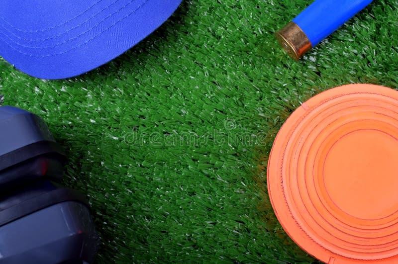 Latający celu talerz, nakrętka, hałasów hełmofonów stłumienie i patron na trawie, obrazy royalty free