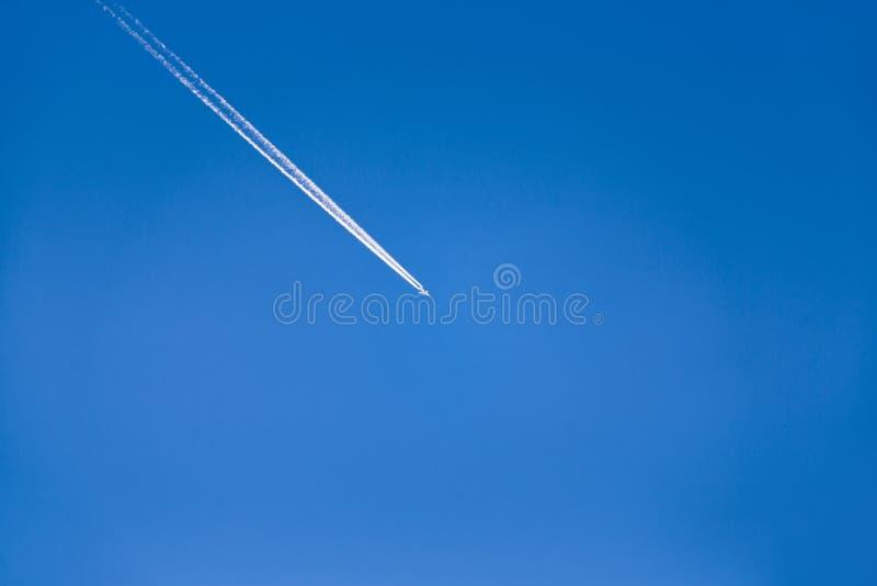 Latający samolotowy opuszcza diagonalny ślad na jasnym niebieskim niebie bez chmur obrazy stock