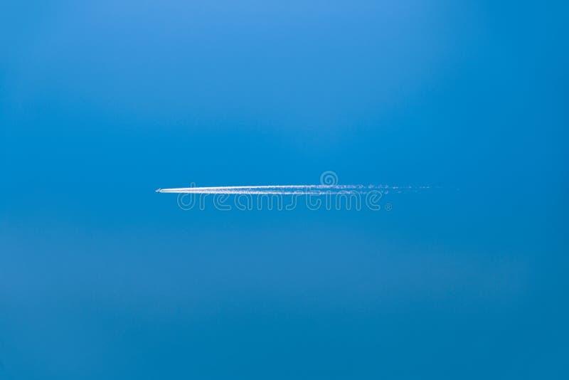 Latający samolotowy opuszcza diagonalny ślad na jasnym niebieskim niebie bez chmur obrazy royalty free