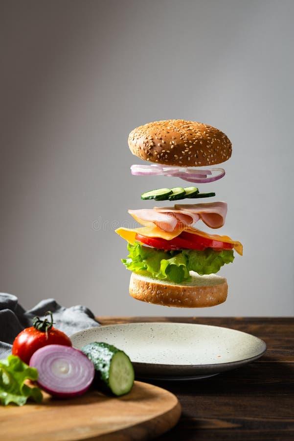 Latający składniki hamburger lub cheeseburger nad talerz z składnikami na drewnianej tnącej desce na ciemnym tle hamburger obraz royalty free